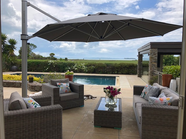 outdoor cantilever umbrellas seen over lounge suite